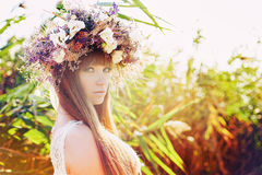 Girl in a wreath. Beautiful girl with long brown hair in ethnic wreath of wildflowers, it is warm autumn colors and a white transparent dress against the Royalty Free Stock Photos