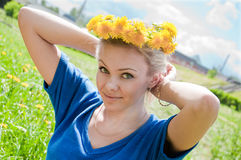 girl with a wreath of dandelions Stock Photos