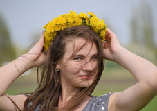 A girl with a wreath of dandelions on her head. Beautiful fairy young girl in a field among the flowers of tulips. Stock Photography