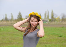 A girl with a wreath of dandelions on her head. Beautiful fairy young girl in a field among the flowers of tulips. Stock Images