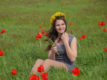 A girl with a wreath of dandelions on her head. Beautiful fairy young girl in a field among the flowers of tulips. Royalty Free Stock Images
