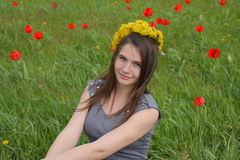 A girl with a wreath of dandelions on her head. Beautiful fairy young girl in a field among the flowers of tulips. Stock Photos