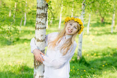 A girl with a wreath of dandelions on her head is standing by th Stock Images