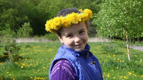 Girl in a wreath from dandelions turns and smiles stock video footage
