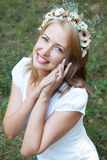 Girl in a wreath of flowers on a background of forest green Royalty Free Stock Photography