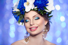 Girl with a wreath of flowers on her head on a blue background o Stock Photography