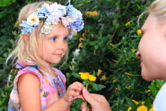 Girl with a wreath of flowers look at mom Royalty Free Stock Photos