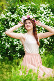Girl in a wreath of flowers near a flowering bush in spring Royalty Free Stock Photography