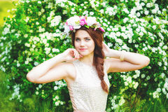 Girl in a wreath of flowers near a flowering bush in spring Royalty Free Stock Images