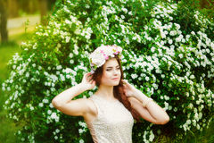 Girl in a wreath of flowers near a flowering bush in spring Stock Images