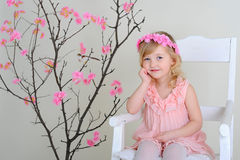 Girl in a wreath of flowers in pink dress sitting on a chair smi. Girl in a wreath of flowers in pink dress sitting on a chair near a flowering tree with a bird Royalty Free Stock Photos