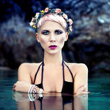Girl in a wreath of flowers in the sea Royalty Free Stock Images