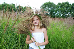 Girl in a wreath of grass with spikelets Stock Photos
