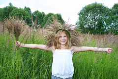 Girl in a wreath of grass with spikelets Stock Image