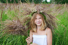 Girl in a wreath of grass with spikelets Royalty Free Stock Image