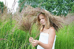 Girl in a wreath of grass with spikelets Royalty Free Stock Photos