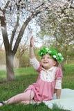 Girl in wreath having fun under tree Stock Images
