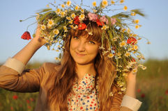 Girl with a wreath on head. Girl with a wreath of daisies and poppies on her head, smiling Royalty Free Stock Photography