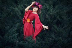 Girl with a wreath on his head. Girl with a wreath on his head in a red dress. She is fabulous fairy Stock Images