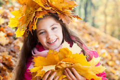 Girl in a wreath of maple leaves Royalty Free Stock Images