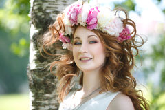 girl in a wreath of peonies with developing hair in the wind Stock Images