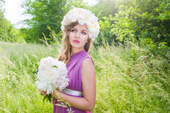 Girl with a wreath of peonies on her head Stock Image