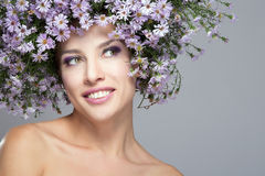 Girl in a wreath of purple daisies Stock Photography