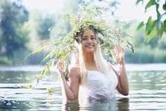 Girl with wreath in a river Stock Images