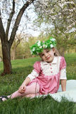 Girl in wreath sitting under spring tree Royalty Free Stock Photos