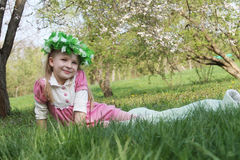Girl in wreath sitting under spring tree Royalty Free Stock Photo