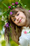 Girl with wreath smiles. Little girl in white sweater has dressed flower wreath on head Royalty Free Stock Photo