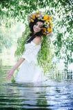 Girl in a wreath splashing in water Stock Image