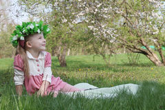 Girl with wreath under spring tree looking up Royalty Free Stock Image