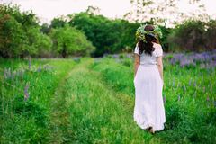 Girl with a wreath of wildflowers on her head walks royalty free stock photos