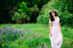 Girl with a wreath of wildflowers on her head walks stock photography