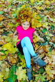 Girl with a wreath of yellow leaves lying on the leaves Royalty Free Stock Photo