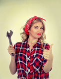 Girl with a wrench retro. The blonde holds a wrench on a white background Royalty Free Stock Photography
