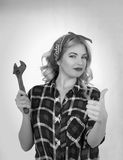 Girl with a wrench retro. The blonde holds a wrench on a white background Stock Image