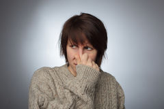 Girl wrinkles her nose from the stench or odor Royalty Free Stock Images