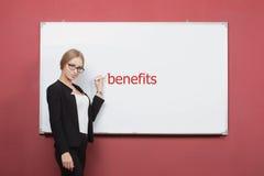 Girl writes benefice on a white board. Stock Photo