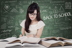 Girl writes on the book while reading Royalty Free Stock Photos