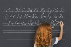 Girl writes in chalk on a black board. Stock Images