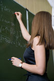 The girl writes chalk on a blackboard Stock Images