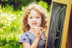 Girl writes in chalk on a blackboard. Stock Photos