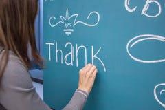 Girl writes chalk congratulation on the blue board Stock Photo