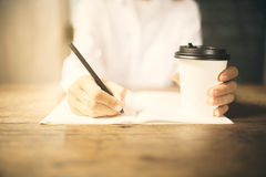 Girl writes in a diary with cup of coffee Stock Photography