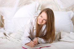 Girl writes a diary while lying Stock Image