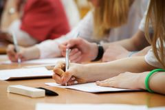 The girl writes with a fountain pen on a piece of paper during classes at school or college. Examination, exams stock photography