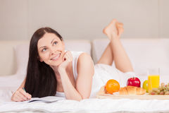 Girl writes having breakfast in bed in morning. Royalty Free Stock Photos