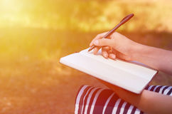 A girl writes her hand in a notebook. Study and work in the park Stock Photo